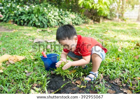 Blond boy of 2 years having fun with gardening and planting vegetable plants and flowers in garden, outdoors. Active leisure with kids, learning gardening and environment. - stock photo
