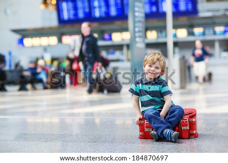 Blond boy of 2 years sitting on suitcase at the airport, indoors and waiting for going on vacations. - stock photo
