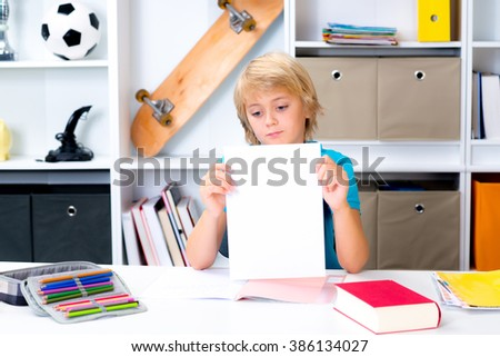 blond boy on desk with bad report card - stock photo