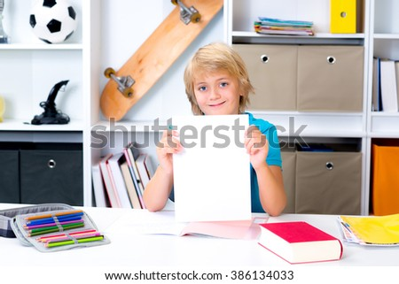 blond boy on desk with good report card - stock photo