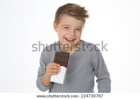blond boy satisfied after biting a chocolate bar - stock photo