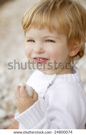 Blond boy smiling portrait on a rolling stones background - stock photo