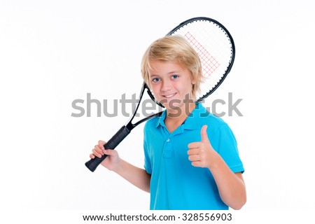 blond boy with tennis racket and thumb up in front of white background - stock photo