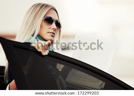 Blond business woman with financial papers at the car - stock photo