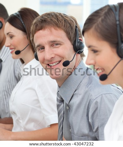 Blond businessman smiling at the camera in a call center - stock photo