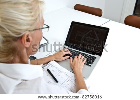 Blond businesswoman sitting and working on here laptop - stock photo