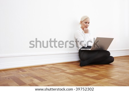 Blond businesswoman sitting on the floor with laptop - stock photo