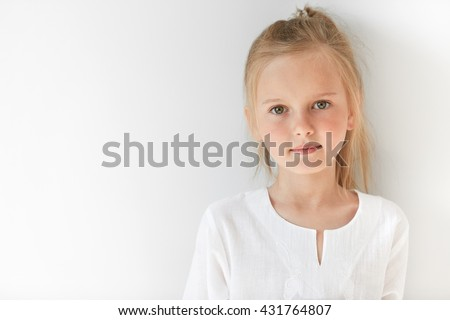Blond Caucasian female child with green eyes standing quietly indoors and looking straight forward in good and sunny day. White colors make little girl look like a little angel or innocent baby. - stock photo