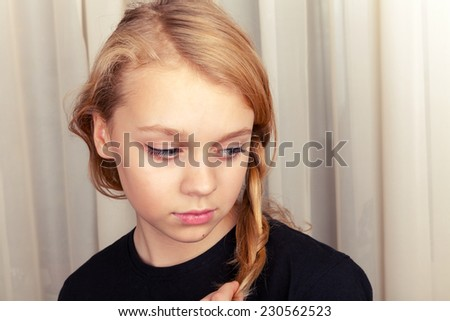 Blond Caucasian girl smiles shyly, close up portrait - stock photo