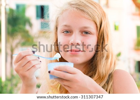 Blond Caucasian teenage girl eats frozen yogurt, close up outdoor portrait with natural light - stock photo