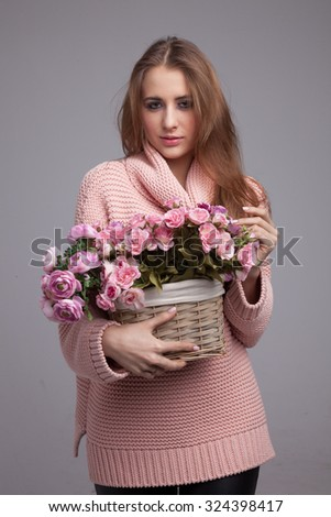 Blond cheerful young pretty woman. Beauty portrait, perfect makeup. Long chic elegant hair. Model tests. Cute girl in pink sweater. Isolated. With flowers. - stock photo