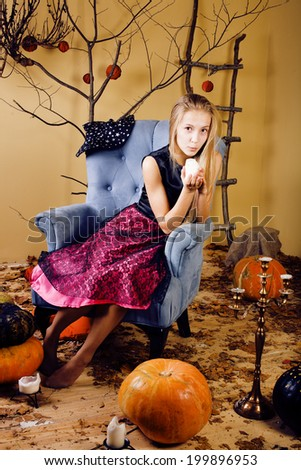 blond cute girl in halloween interior with pumpkin - stock photo