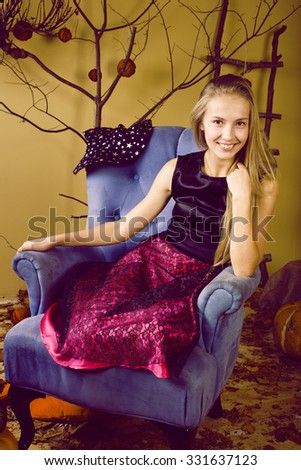 blond cute girl in halloween interior with pumpkin smiling, teen celebration - stock photo