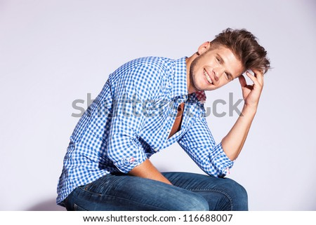 blond fashion male model sitting and laughing on gray background - stock photo