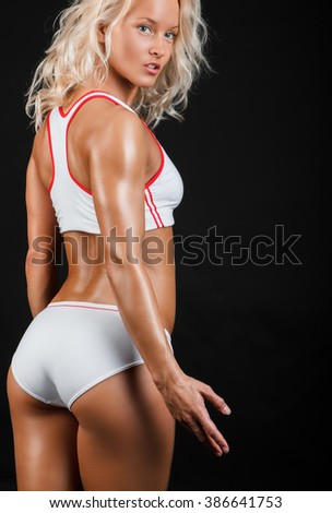 Blond female in a white sexy sportswear isolated on a black background. - stock photo