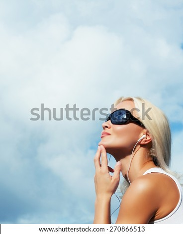Blond female in sunglasses listening music. - stock photo