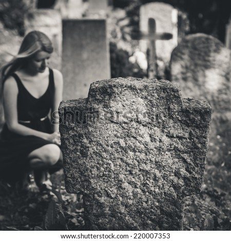 Blond girl at grave. Black / white cemetery shot. Selective focus. - stock photo