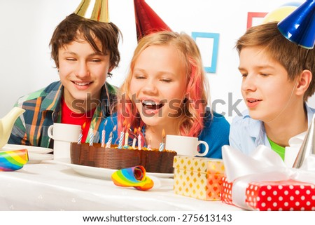 Blond girl blows candles on her birthday cake - stock photo