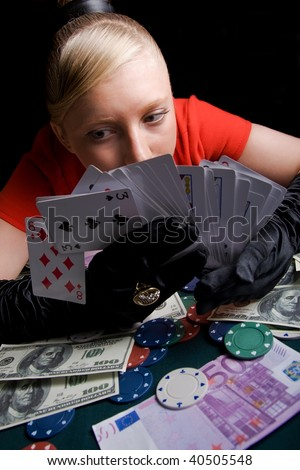 Blond girl holding bunch of playing cards - stock photo