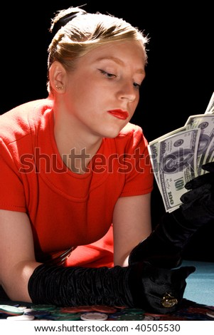 Blond girl holding large sum of dollar cash - stock photo