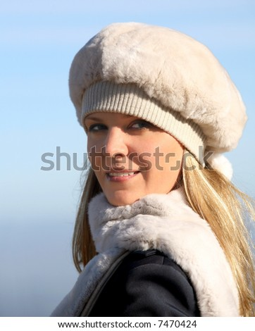 Blond girl in a fur hat and a scarf - stock photo
