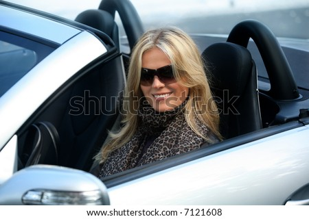 Blond girl in sunglasses driving convertible car - stock photo