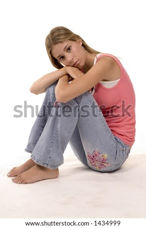 blond girl in thought - sitting in casual jeans - stock photo