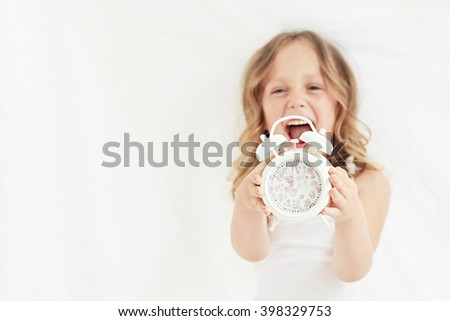 blond girl in white t-shirt and white pants is waking up  - stock photo