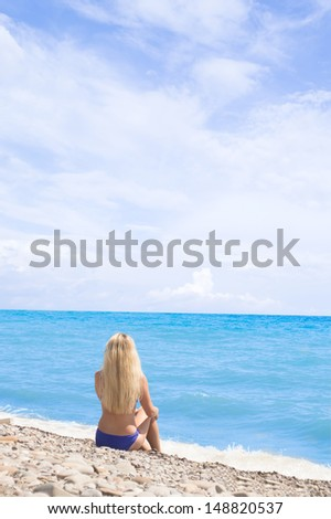 blond girl looks into the distance while sitting on the sea shore - stock photo