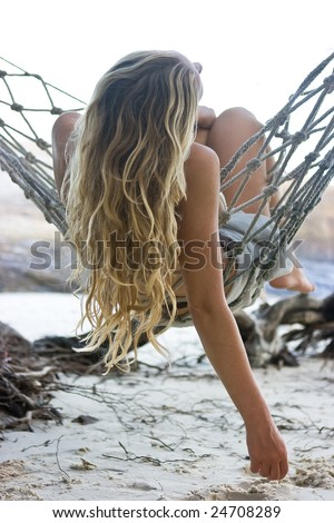 Blond girl lying in hammock on the beach - stock photo
