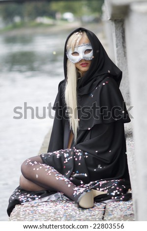 blond girl near river under black hood with colored confetti all around - stock photo