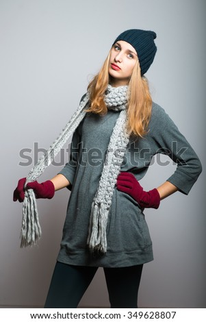 blond girl pulling a winter scarf, Christmas and New Year concept, studio photo isolated on a gray background - stock photo
