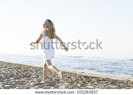 Blond girl running along the shore on a beach with a blue sky in the background. - stock photo