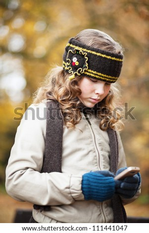 Blond girl texting with her cellphone while walking in an autumn park - stock photo