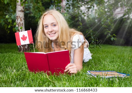 Blond girl with a book and Canadian flag lying on the grass - stock photo