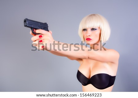 blond girl with a gun - stock photo