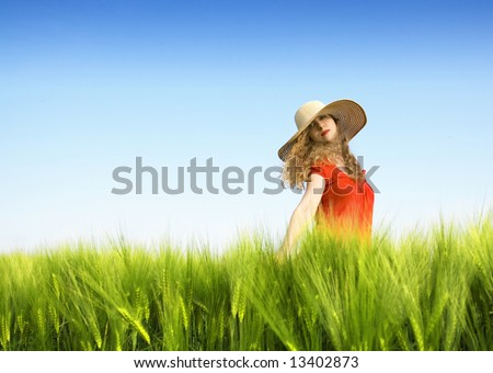 blond girl with big hat in a green wheat field against blue sky - stock photo