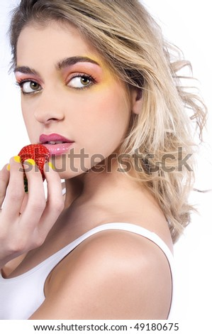 Blond girl with colorful make-up holding strawberry - stock photo