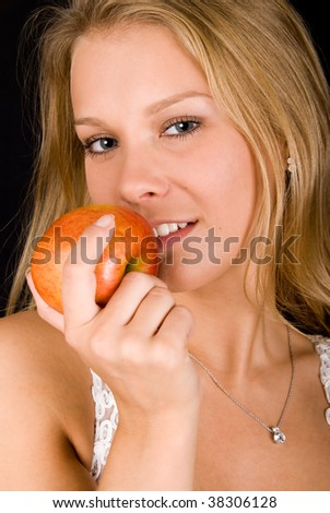 Blond girl with red apple looking at camera - stock photo