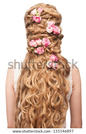 Blond Hair. Beautiful Caucasian Woman with Curly Long Hair. Bridal hairstyle decorated by flowers - stock photo