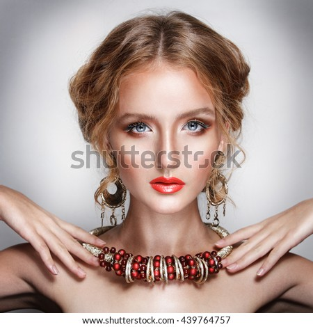blond hair beauty woman portrait wears golden ear-rings and necklace in luxury sexy style fashion model on grey background - stock photo