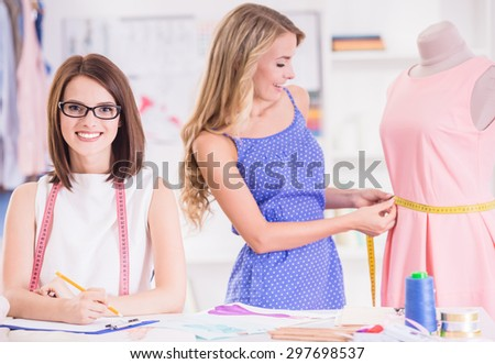 Blond hair woman taking measurement with mannequin and brown hair woman in glasess writing it down. - stock photo