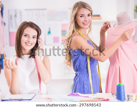 Blond hair woman working at pink dress on mannequin and brown hair woman speaking by phone in studio. - stock photo