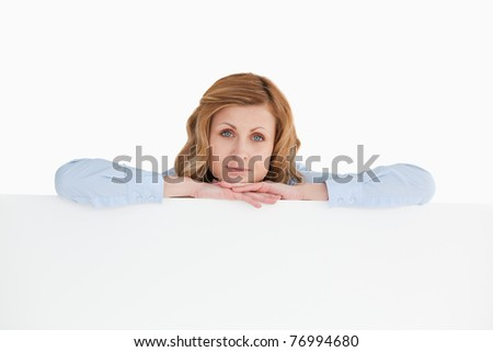 Blond-haired woman posing while leaning against an empty white board - stock photo