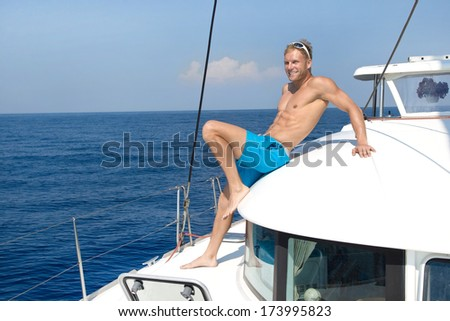 Blond handsome young man on sailing boat. - stock photo
