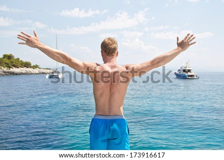 Blond handsome young man standing on a sailing boat - ready to j - stock photo
