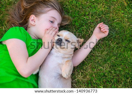 Blond happy girl with her chihuahua doggy portrait lying on lawn - stock photo