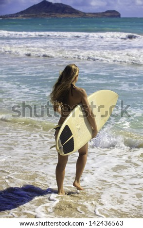 blond in bikini with her surfboard heading into the waves in hawaii - stock photo