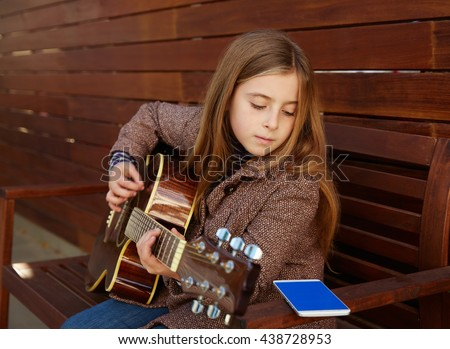 blond kid girl learning play guitar with smartphone winter beret on wooden background - stock photo