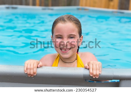 Blond kid girl swimming in the pool with sun tan red cheeks - stock photo